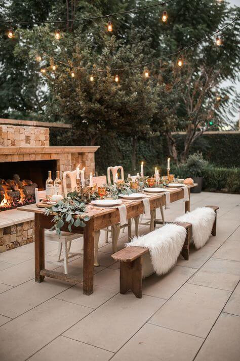 An outdoor tablescape. The table is rectangular and made of dark wood with matching bench seats. White fluffy rugs rest in the bench seats. The table has a long green foliage runner, with candles and white table settings. The ground is stone pavers with an ourdoor fireplace behind the table, set with red bricks. Dark green trees are in the background with fairylights strung between them