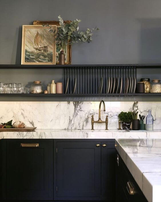 A corner kitchen bench. The benchtop is white marble with black cupboards underneath with brass handles. A white marble splash back matching the bench is above, with two black floating shelves on a black painted wall above. On the lower shelf there is an assortment of plates resting sideways as well as some glasses and small vessels. On the shelf above there are two framed oil paintings of some boats with a small vase and native greenery hanging out. On the bench there are some knick knacks and a gold tap is visible above a sunken sink.