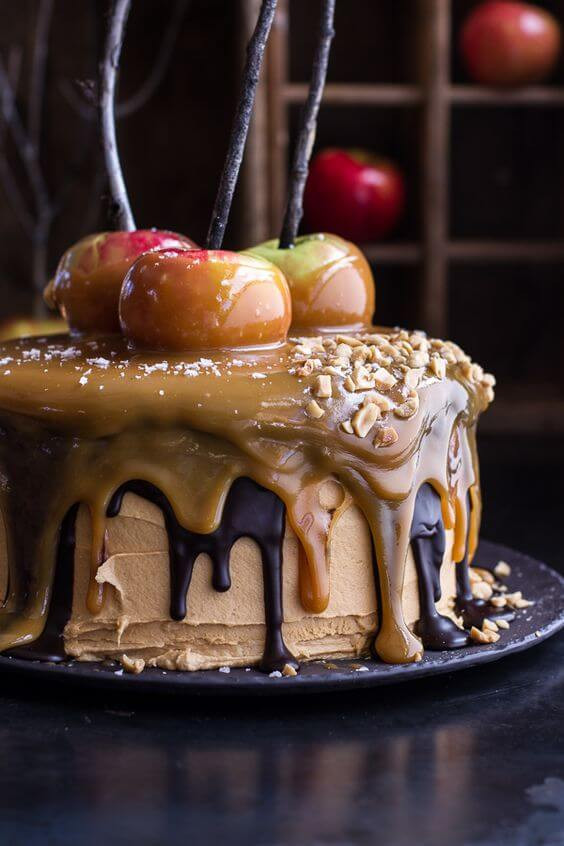 A dessert rests on a black dining plate. It resembles a round cake with dripping chocolate and caramel down the sides. Toffee apples rest on top.