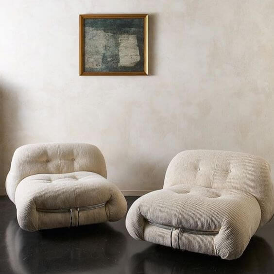 Two mid century single seat sofas are resting on a cream wall. The sofas are beige and corderoy with buttons on the seat and back. A framed painting hangs on the wall and the floor is black.