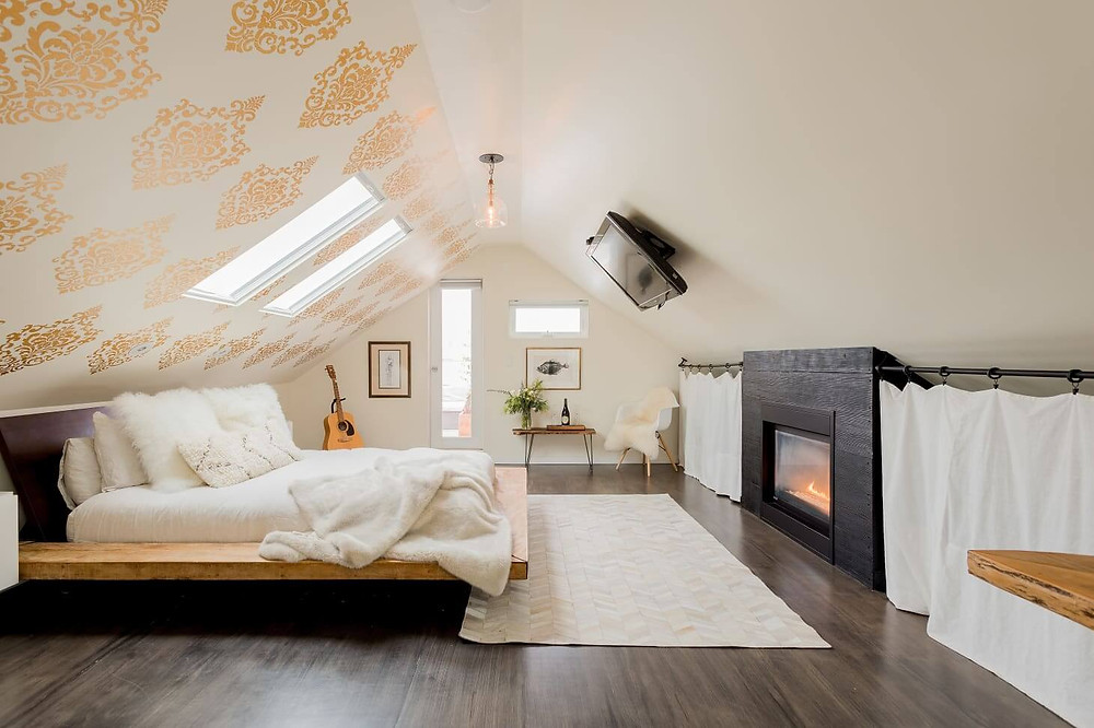A loft style bedroom. The floor is a dark timber. The walls are beige; the ceiling is sloped to a point in the middle. The right ceiling slope matches the beige of the walls and has a TV mounted to it. The other ceiling/wall has gold damask wall paper with two large inset windows. A pendent light hangs from the middle of the roof. A bed sits in the middle of the room opposite the TV; it has white sheets with a wooden base and fluffy white cushions. Artwork hangs on the far wall with a clear-glassed door and a rectangular window. An acoustic guitar sits in a stand in the far corner. Opposite it there is a side table with a plant and a lush white arm chair. There is a fire place opposite the bed and a white rug rests at the foot of the bed