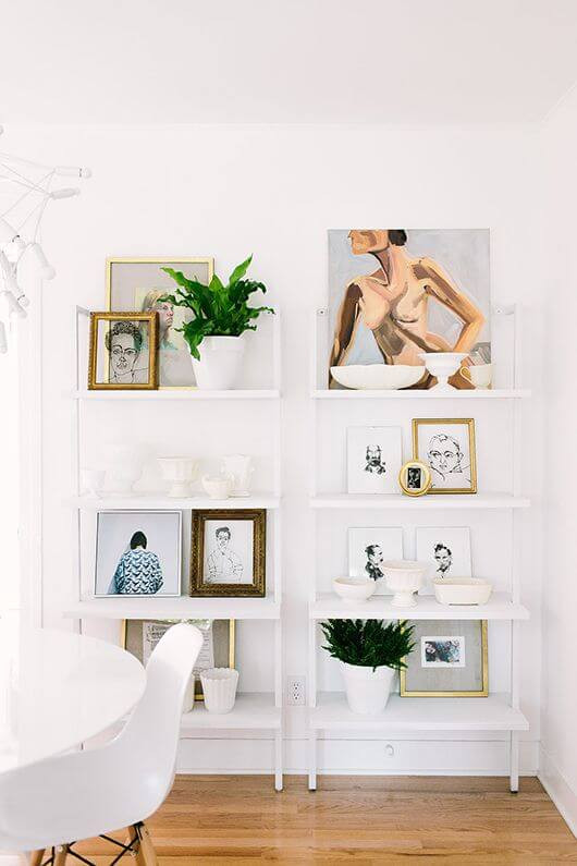 Two white ladder shelves lean against a wall. Various artworks and pot plants adorn the shelves. A white dining table with a white chair sits in the foreground.