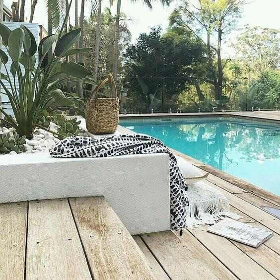 An outdoor pool and deck. In the foreground there is a staircase in light timber decking leading down to a decked area and pool on the right. The pool is rectangular and filled with turquoise water. There is a cream garden edge next to the stairs. A black and cream coat lays on top with a straw handbag. The garden has a fern and a few smaller cactus style plants and is filled with white pebbles. In the background there is a clear pool fence with lots of green trees and shrubs beyond.