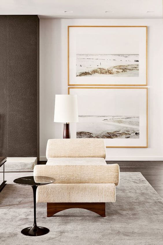 A lounge room with a slim black coffee table, a cream single-seat sofa and a lamp with a white lampshade. A grey rug sits on the floor, while two gold-framed beach images hang on the wall.