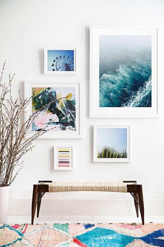 A photo of a wall with five photographs of different sizes hanging in white frames with white matts. The photos depict an ocean, a ferris wheel, a fern tree and 2 abstract paintings. A brown wood and cane bench sits in front on a white floor. A multi coloured rug is in the foreground with colours from the photos - cream, aqua, pink. A white vase sits on the left with dried flowers.