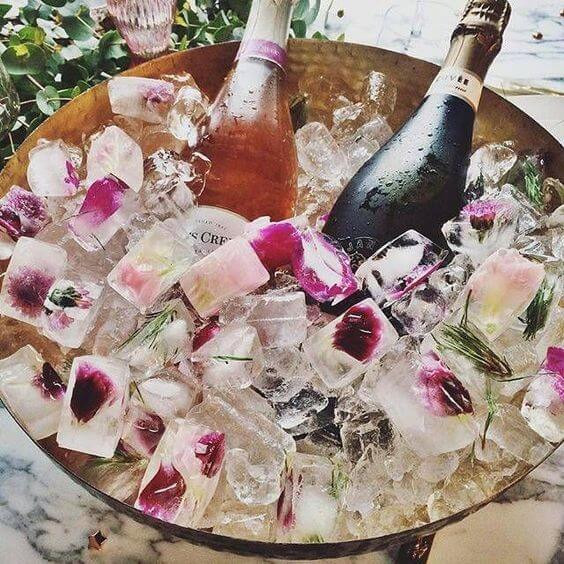 A large copper ice bucket is filled with ice that has pink flower petals frozen inside. A bottle of wine and pink champagne rest in the ice
