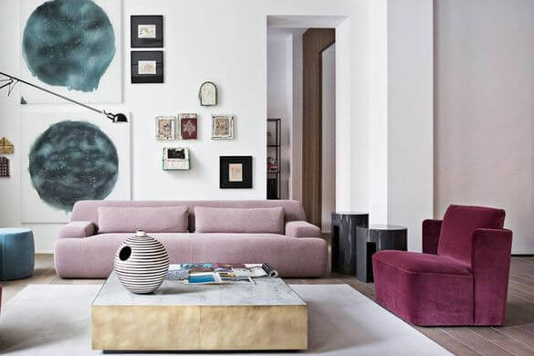 An interior living room. A dusty pink two seater sofa is at the back of the room with a plum colours matching single seater to the right. A gold coffee table with a marble bench top is between the sofas, sitting on a simple shite rug. An assortment of paintings hang on the back wall which is painted white. The floor under the rug is timber and the wall to the right is painted a soft pink.