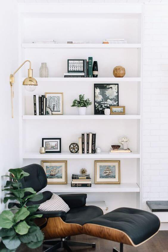 A corner of a room with white walls and a timber floor. A large white bookshelf rests on the far wall, with various books, vases and brick a brack resting on the shelves. A black leather and timber eames chair and matching ottoman sit in the corner. A leafy plant is next to it and a small gold lamp with a naked bulb rests over the chair, attached to the wall.