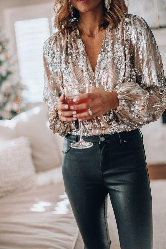 A woman with tan skin stands in black leather pants and a sparkly champagne coloured top. She is holding a wine glass filled with an orange liquid and is wearing some silver rings. Sparkly gold dangly earrings hand from her ears and a simple gold necklace is around her neck. In the background there is a beige couch and the edge of a window
