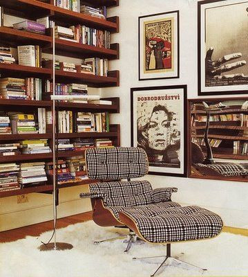 A photo of a study. Large timber bookshelves line the left wall, filled with books. The right wall is painted white and has assorted framed prints hanging on it in different sizes. A white fluffy rug sits in the middle of the space with a timber and plaid fabric eames chair and ottoman sitting on top. A silver tall standing lamp is on the left of the chair.