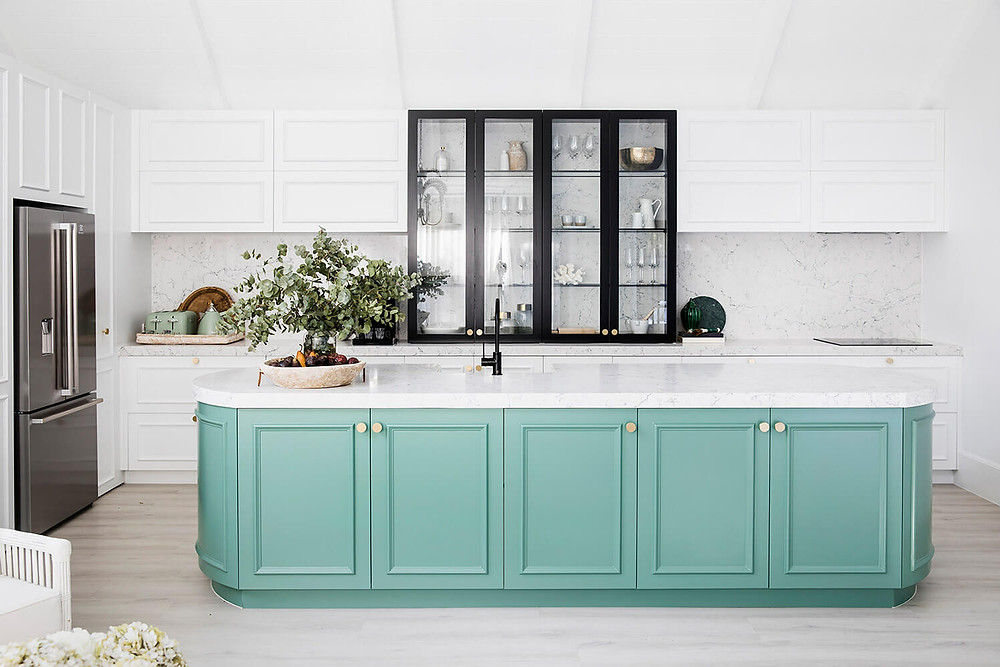 A kitchen. The floor is a light grey laminate and an island bench is in the middle of the room. It has a white stone benchtop with a sunken sink, black tapware, mint green under cupboards with gold round handles and a bonsai plant resting on the left of the bench. Behind the island bench is a long white bench resting against a wall. It has white cupboards underneath and floating above, with a white tiled splash back. A black china cabinet is in the middle of the bench filled with wine glasses. A stainless steel fridge is on the left.