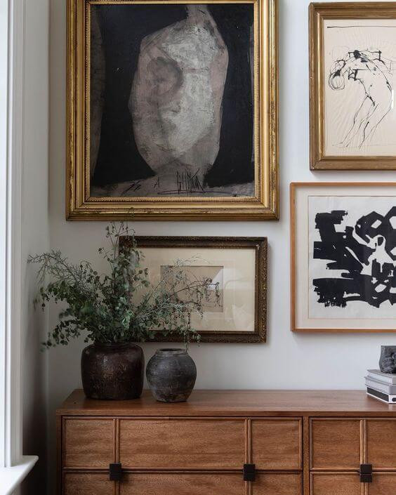 A cream wall with an assortment of paintings hanging in brown timber and gold frames. A wooden side table rests against the wall with two simple vases with leafy grennery.
