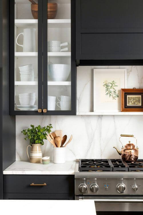 A close up of a kitchen bench. The bench top is white stone with black drawers underneath and brass handles. A vessel with a green plant and another with wooden spoons rest on the bench. There is a grey marble splash back and above that an inset black china cabinet, filled with white crockery. On the right there is a stainless steel oven with a copper kettle sitting on the stove; a  white floating bench sits above it with two framed artworks sitting on the shelf.