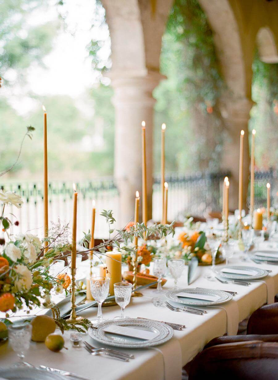 An outdoor tablesetting. The long rectangular table has a white linen tablecloth, with orange and cream flower arrangements, long tapered honey coloured candles and grey dining plates on top. In the background are stone archways and blurred foliage.
