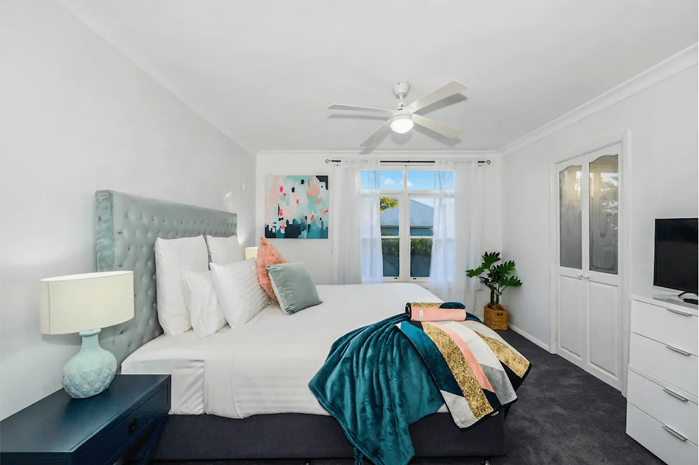 A bedroom. A queen bed with white sheets sits in the middle of the room. It has a pale aqua fabric headboard with a dark teal and patterned blanket laid on the end of the bed. Multiple white pillows and cushions adorn the bed with a matching aqua cushion and a coral cushion in the centre. A black side table is visible to the left of the bed with a blue lamp on top; it has a cream lamp shade. The walls and ceiling are all painted white and the floor is grey carpet. A white tallboy is opposite the bed with a small tv on top. Abstract blue and coral artwork hangs on the adjacent wall. There is a white ceiling fan/light on the ceiling and a window with white frames on the back wall.