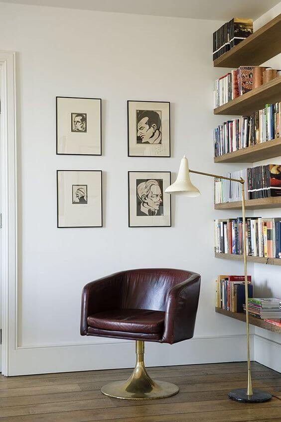 A corner of a room, set up as a book nook. The walls are white and the floor is timber. One wall has four framed prints in neutral tones handing in a square formation. The other wall has shelves, attached to the wall with no base, in a natural timber, filled with an assortment of books. A brown leather ball chair rests in the corner with a brass bottom. A gold overhanging lamp with a simple cream shade rests over the chair.