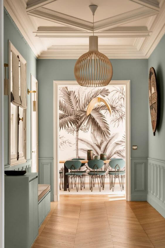 A wide hallway with a dining room visible at the back. The floor is light brown floorboards in a chevron pattern and the walls are painted mint green. The ceiling and trims are cream and a beige round pendant light hangs from the ceiling. There is a window on the left wall with beige blinds and a large artistic piece hanging on the right wall. In the dining room beyond there is wall paper of brown palm trees on the wall, along with a wooden dining table and chairs upholstered in the same colour as the mint green/teal walls.