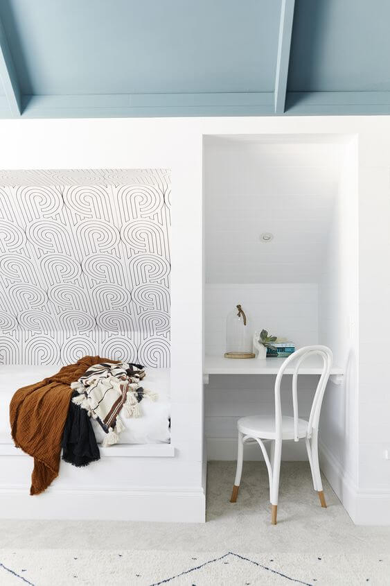 A small study nook is inset in a white painted wall. The alcove includes a white desk with a white metal chair. There is another small alcove to the left with a white bench seat, a brown blanket thrown on top, and patterned black and white spiral wallpaper in the alcove wall. The ceiling above is painted teal and the floor is beige tiles
