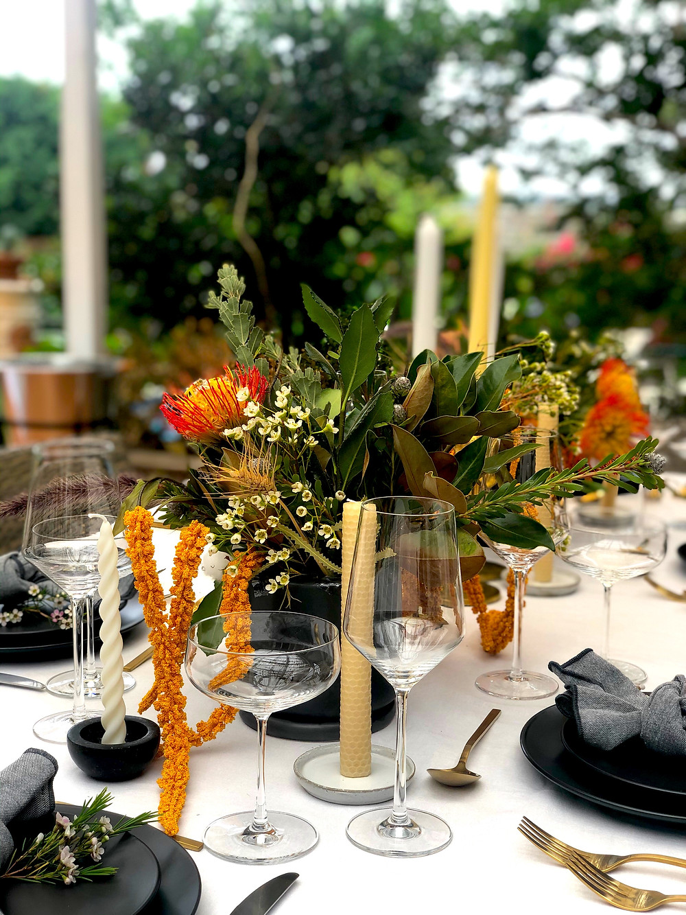 An outdoor table setting. There is native Australian flora on the table atop a white tablecloth. There are natural beeswax candles and black dinging plates with gold cutlery