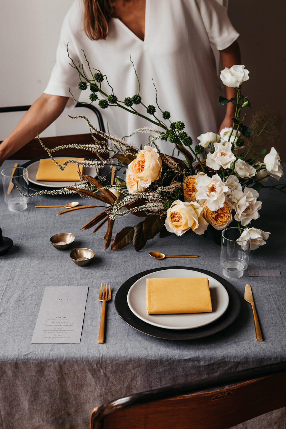 A woman in a white shirt works on a table setting. The rectangular table has a grey tablecloth, black and white dinner plates with mustard coloured napkins on top, gold cutlery, a printed item to the left of each place, and yellow and white flowers arrangements.