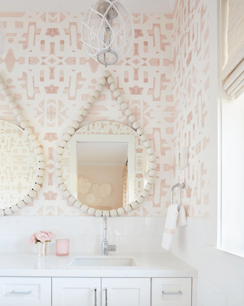A white bathroom vanity sits against a wall with white tiles above and on the adjacent wall. On the wall above the vanity is a soft blush pink and white wall paper in an aztec style pattern. Two circular mirrors hand on the  wall surrounded by cream wooden beads. a simple silver hand towel rail is attached to the wall on the right with a white handtowel hanging from it. There is an open window to the right and blush pink accessories on the vanity. A small orb shaped light hangs from the ceiling with white macrame decor on the outside of the glass