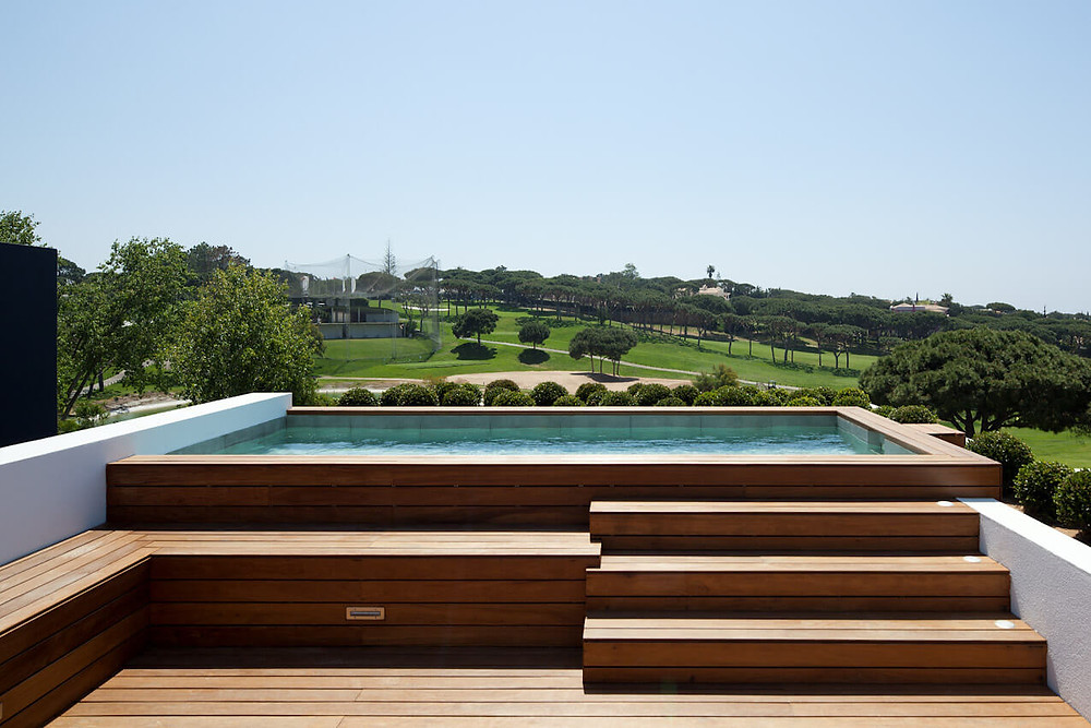 A photo of an outdoor pool. In the foreground there is timber decking and a bench seat/storage space. Timber stairs lead up to an above ground pool. It is surrounded by the same timber decking with white retaining walls either side. The pool is filled with turquoise water and overlooks a majestic view of green hills, tan gravel paths and lots of trees.