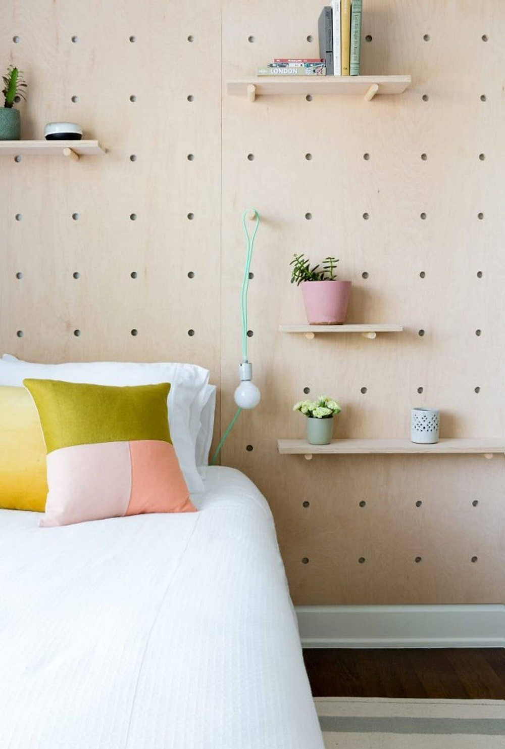 A close up of part of a bed with a large light wood peg board behind it. On the pegboard are multiple floating shelves with pot plants, books and knick knacks on them. The bed has white sheets, pillows and doona with colourful green and pink cushions.