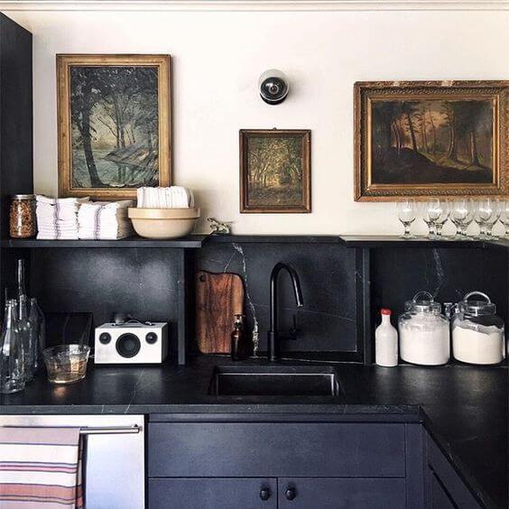 Three framed photos of woodlands hang on a wall in a kitchen. The kitchen cabinetry and sink are black. Assorted kitchen items sit on the bench including a jar of sugar and a wooden chopping board.
