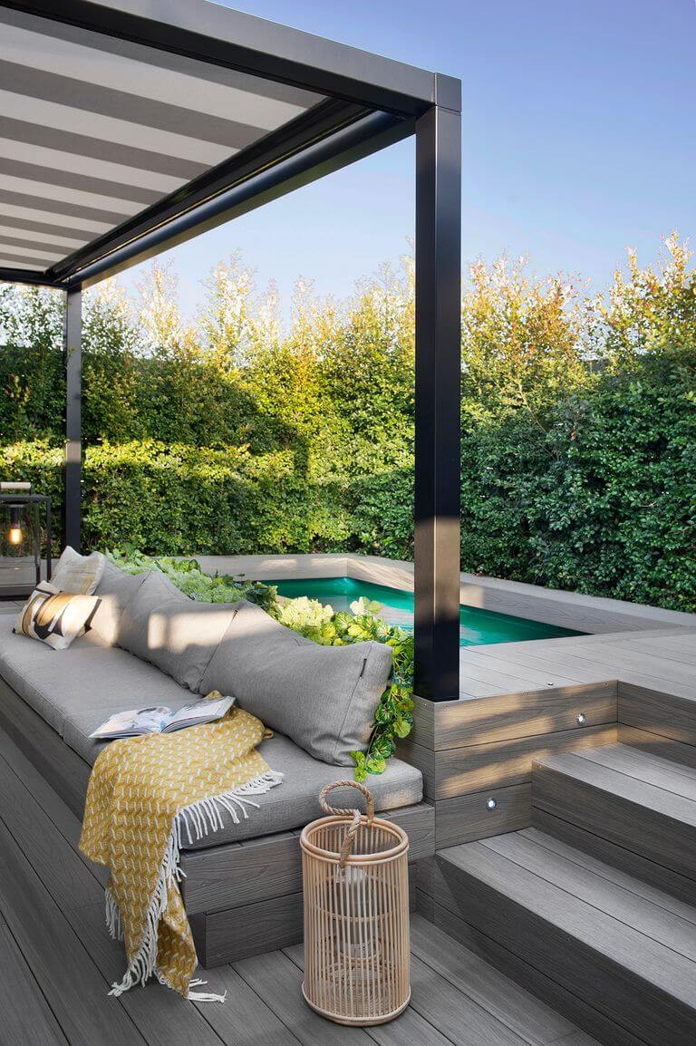 A photo of an outdoor pool area at an angle. In the foreground is grey decking and steps leading up to the pool area. An orange candle holder sits on one of the steps. There is a grey bench built into the decking with a grey cushion seat and back. A yellow towel is thrown on the bench. A black pergola sits above the deck. A small outdoor pool is seen in the far corner surrounded by green bushes.