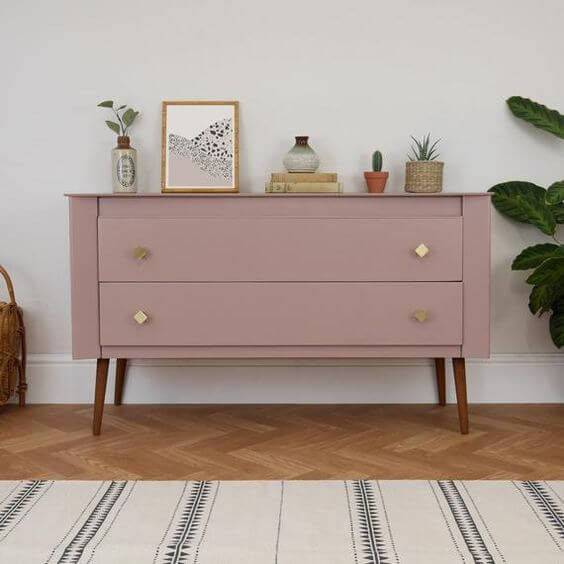 A pink hall table rests against a white painted wall. The table is painted dusty pink and has two drawers with gold diamond shaped handles. The legs are natural timber and are tapered, attached at angles to each corner. Assorted items sit on top of the dresser - a framed print, a vase with a leafy plant, some books, a cactus. The floor is timber chevron and a striped cream and blue woven rug is in the foreground.