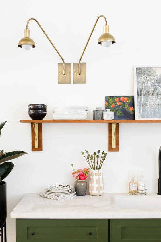A close up of a kitchen bench. The benchtop is white stone with olive green cupboards underneath. The wall behind is painted white with a floating timber shelf attached. On the shelf are assorted artworks and knick knacks. On the bench are a few vases with plants and some bowls. There are two gold hanging lights attached to the wall above the shelf.