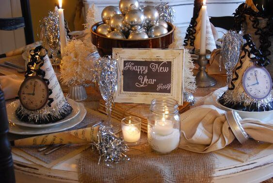 A close up of a round upcycled table painted white and sanded back with intentional scuff marks. A brown hessian runner is on the table with an assortment of decorations: party hats made with sheet music, silver tinsel and images of clocks with curly black ribbon coming out of the top; votive candles, tea light csndles in jars; beige linen napkins with silver napkin holders; a brown wooden bowl filled with silver baubles; champagne glasses filled with silver streamers; and a black chalkboard in a cream frame with 'Happy New Year written on the board