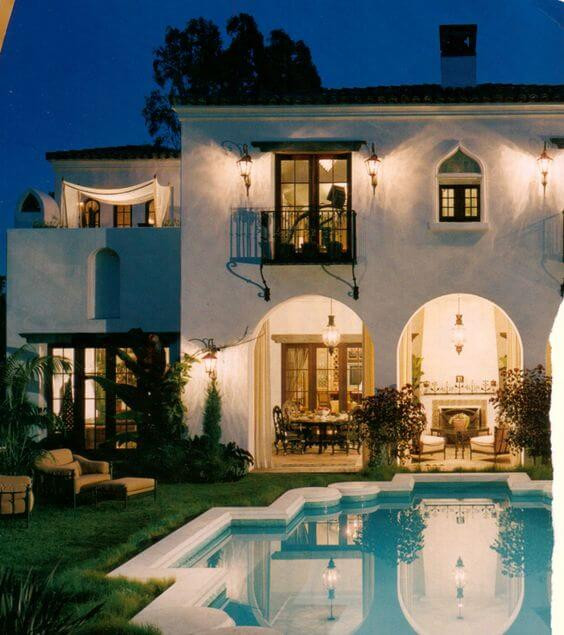 A photo of a backyard at night. A unique Moroccan tile  shaped pool is in the foreground. It is surrounded by white tiles and filled with clear turqoise water. A manicured green lawn is on the left. Behind the pool is a two storey cream house with archways on the ground floor and lots of top windows. There are lights on casting a soft amber glow onto the pool.