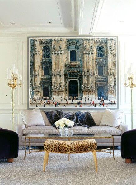 A large print of a cathedral wall hangs on a wall above a beige lounge. Assorted grey and cream cushions adorn the lounge, with a leopard print footrest in front