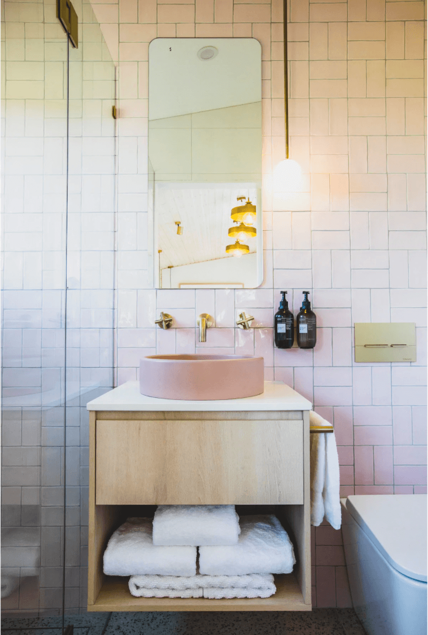 A close up of a bathroom vanity. The vanity is brown timber with a drawer at the top and an open space at the bottom filled with white towels. The sink is pink stone with gold tapware attached to the wall. Above the vanity rests a rectangular mirror with rounded edges. Glass shower doors are visible on the left and a white toilet on the right. Organic pump bottles hang on the wall to the right of the sink. The wall is tiled in a soft pink