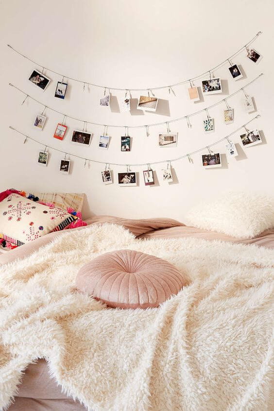 A close up of the side of a bed. It is covered in a soft cream blanket with a round blush pink cushion on top. The wall behind is painted white with string lights hanging on the wall and polaroid photos attached with clips.