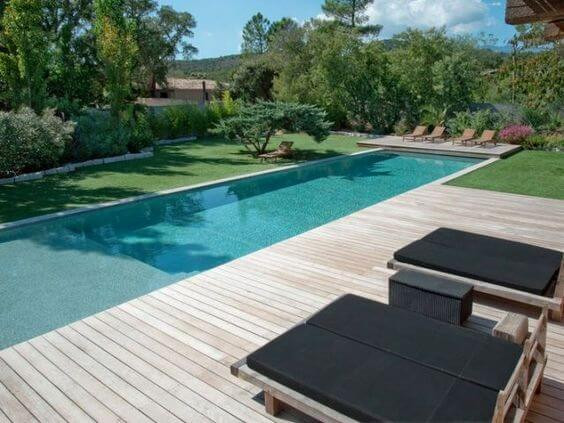 A long, thin outdoor pool filled with turqouise-clear water. The back of the pool and right side are decked in a light timber. There are four brown lounge chairs at the back of the pool and two double sized lounges on the right with black cushions. The left of the pool and next to the back decking is lush, manicured green grass. In the background there is an abundance of green shrubbery