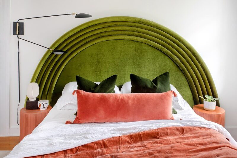 A close up of a queen sized bed. The headboard is a large arch with layers like a rainbow, all in the same velvet green fabric. The bed had white sheets and pillows on it with dark green cushions, a long dusty pink cushion and a matching dusty pink blanket. Two orange/pink bedside tables rest either side of the bed, they are cylindrical with grooved lines around them. On the right one rests a small white pot with a green plant, on the left there is a bowl and an abstract ornament. The wall behind the bed is painted white and a light is attached on the left above the bed with two black light arms.