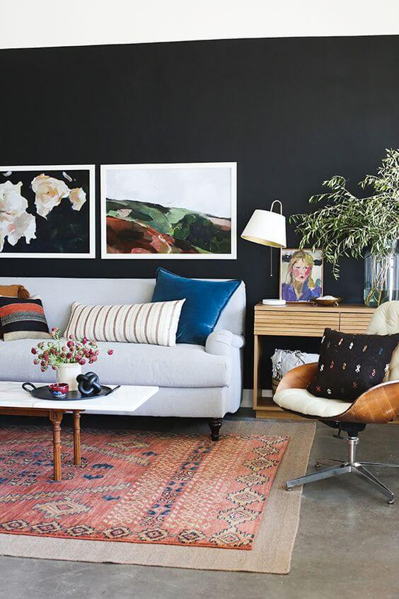 A living room. The floor is grey tiles with a faded red and blue aztec rug. On top of the rug is a white coffee table with wooden legs. A plant rests on top. The back wall is painted black with two large photographs of nature in white frames hanging on the wall. A light grey couch rests against the wall with blue and red cushions. To the right of the couch is a light wooden side table with photographs, plants and a simple table lamp on top. In front of it is a wooden Eames style chair with cream upholstery and a black cushion