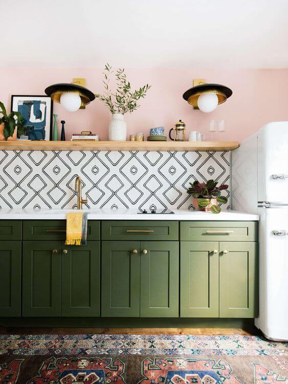 A kitchen. Olive green cupboards rest against a wall with a black and white tiled splashback above. The bench top is a white stone and the sink has gold tapware. A plant sits on the benchtop and a light wooden floating shelf hangs above the tiles. On it are assorted plants, photos and knick knacks. The wall behind the shelf if painted in a light pink with two hanging lights. A traditional patterned rug is on the floor and the side of a vintage white fridge is visible on the right