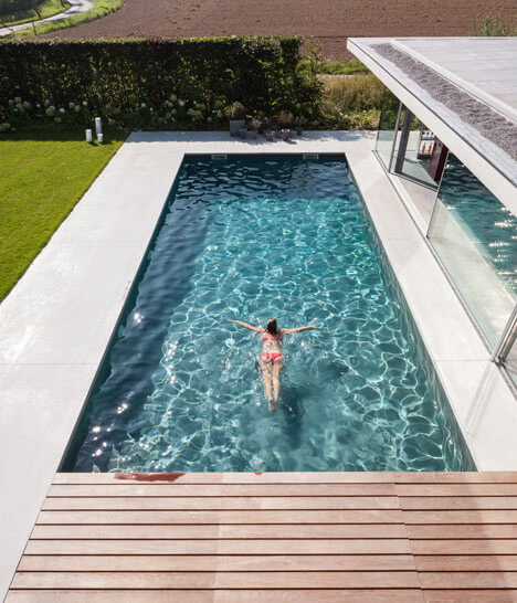 An overhead shot of an outdoor pool. The sun glistens off turquoise water, a lady in a pink bikini has just dived in. White tiles frame the pool with a timber deck in the foreground./ There is a glass pool fence on the right and green manicured lawn on the left.