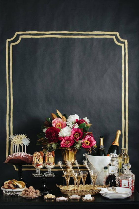 A buffet table with a black table cloth. It rests against a black wall with a gold frame painted behind it. On the table there is a colourful flower arrangement, bottle of champagne in a cream bucket, martinin glasses with sparklers in them and an assortment of food.