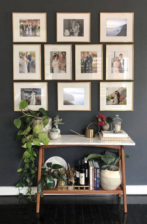 A photo of a wall. The wall is dark grey with 10 framed photos hanging on the wall. The photos feature a family, mostly wedding photos, in gold frames with cream matts. A side table sits under the photos. It has brass legs with a white top. Various plants and books sit on top and on a second shelf underneath.