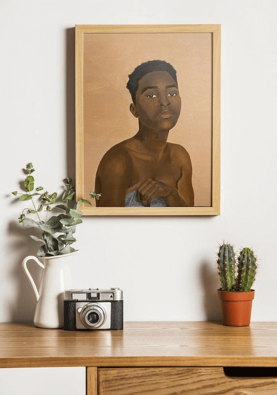 An artwork by artist Charlotte Dyce hangs on a white wall. The artwork is an oil painting of a dark skinned woman with short black hair. The artwork is framed in a tan wooden frame, hanging above a wooden desk featuring a white vase with native flowers, a terracotta pot with a cactus and a vintage camera