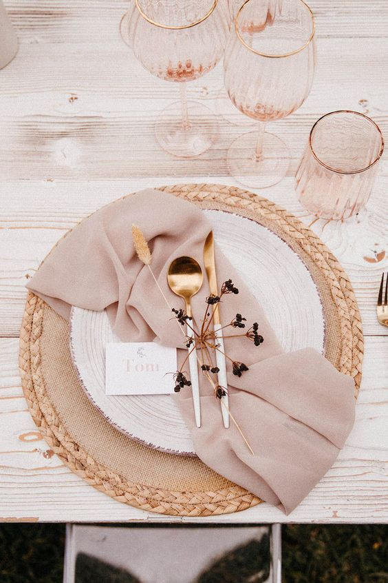 An overhead photo of a place setting at a table. The table is light wood. There is a natural fibred round placemat with a cream dining plate on top. A blush coloured napkin rests across the plate in a haphazard manner with gold cutlery on top. There are three blush coloured glasses with gold rims behind the setting.