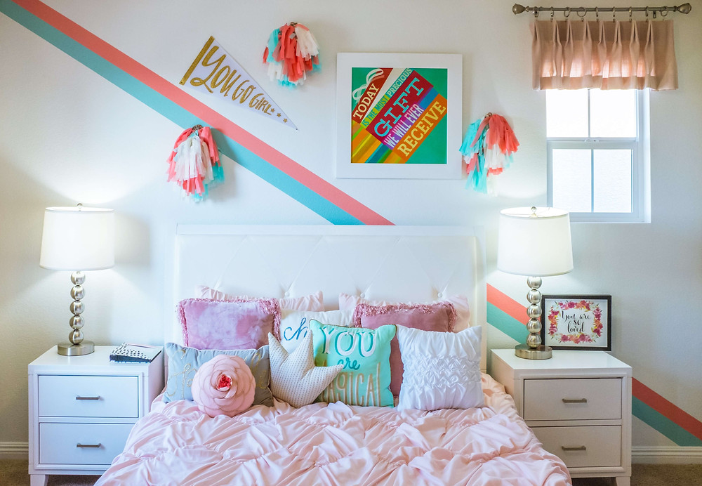 A bedroom. A queen size bed with a cream fabric headboard sits against a white wall. There are white bedside tables either side with two drawers and silver lamps with cream lampshades. The bed has a textured pink blanket and an assortment of pink, cream and teal cushions. Above the bed there is a teal and pink striped wallpaper hung diagonally from the ceiling down to the floor, teal, pink and white cheerleading pom poms on the wall, a 'you go girl' flag with gold lettering and a framed slogan print. On the right bedside table is a framewd quote and a small window with a blush pink curtain is on the right of the wall.