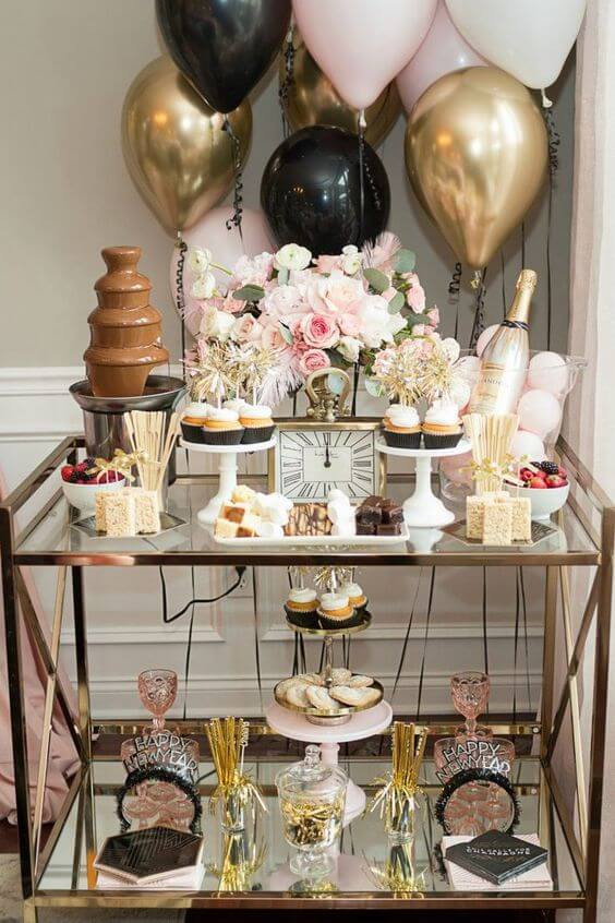 A glass side table with a gold metal frame is used at a party. Gold, black, white and baby pink balloons sit behind the table. On the table there is a pink and white flower arrangement, white cake stands with frosted cupcakes, bowls of strawberries, a chocolate fountain and a bottle of pink champagne. Below the table on the second tier there are pink and gold champagne glasses, Happy new year signs and more cupcakes.