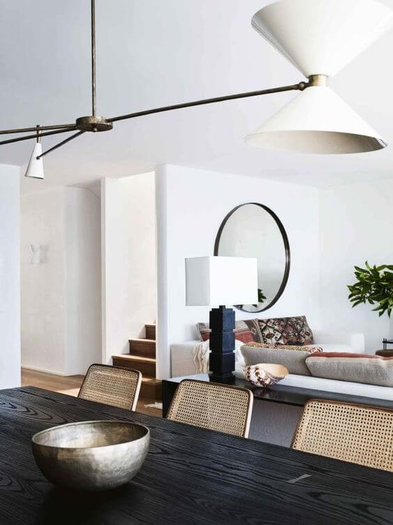 A photo of the same room as the previous image but from a different angle. We now see the room from the other side of the dining table, with a closer look at the pendant light above. In the background there is a set of stairs, a beige couch and a large circular mirror hanging on the wall. A black table lamp with a square white lamp shades rests on a side table