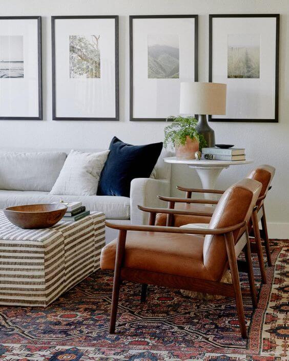 An interior living room. The floor has a large patterned rug in navy blue, faded red and cream. Two vintage chairs sit on the right, they are wooden with brown leather seat and back. A beige couch rests on the fall wall with a white and navy cushion on top. A modern white tall, circular table sits on the right with a small pot plant and a table lamp with a conventional lightshade on top. A striped coffee table is in the middle of the room with a brown wooden bowl on top. The wall above the couch is painting white with four large black frames hanging on it. Inside the frames are four nature photographs with a large white matte