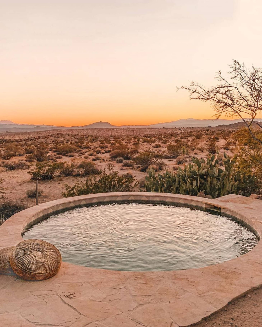 A circular concrete outdoor pool is in the foreground, surrounded by tan pavers. Two round brown cushions lay on the ground next to the pool. The pool overlooks a breathtaking view of Arizona style desert with brown sand and dark green greenery, with a sunset.